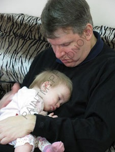 Baby sleeping in father`s chest